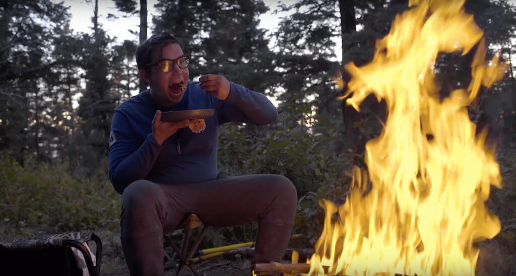 Crew member eating by fire.